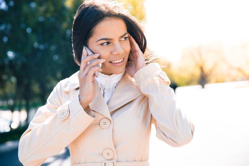 Download Glimlachende Vrouw Die Op De Telefoon Spreekt Stock Foto - Afbeelding bestaande uit holding, mensen: 54082872