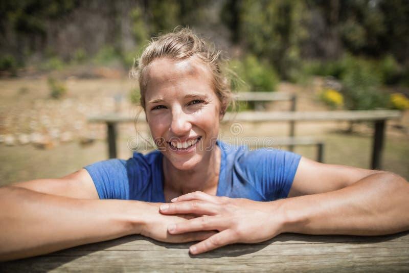 Glimlachende vrouw die op een hindernis tijdens hinderniscursus leunen stock foto's