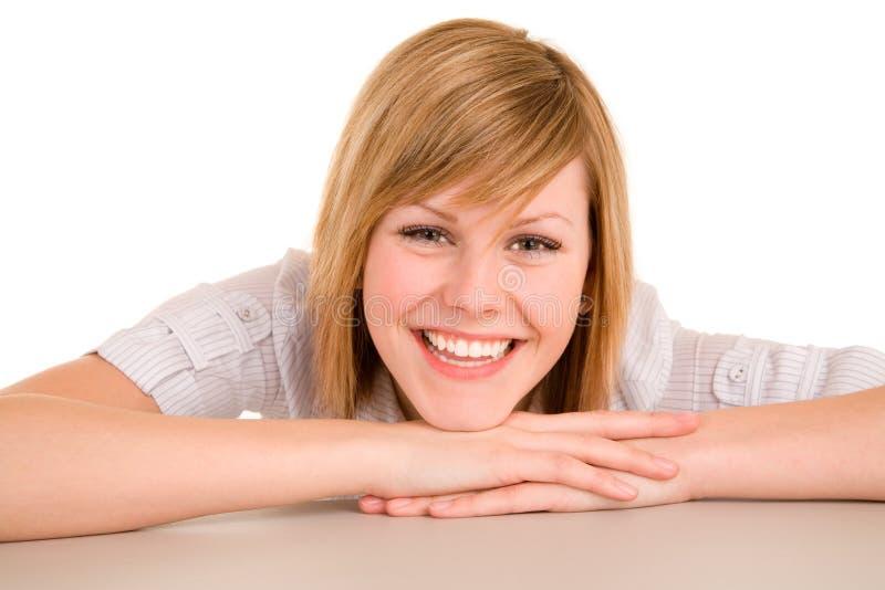 Glimlachende Vrouw die op haar Bureau legt stock fotografie