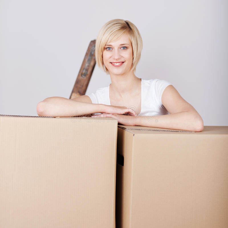 Glimlachende vrouw die op kartondozen leunen royalty-vrije stock fotografie