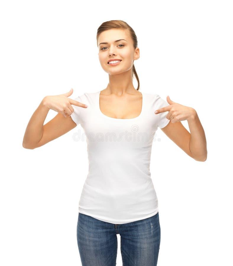 Glimlachende vrouw die op lege witte t-shirt richten royalty-vrije stock foto's