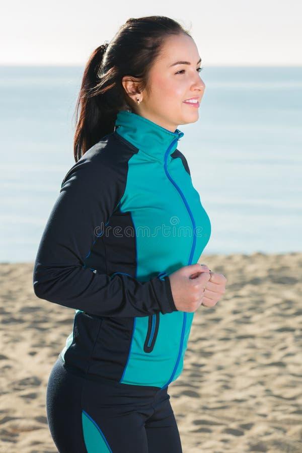 Glimlachende vrouw die op strand lopen royalty-vrije stock afbeelding