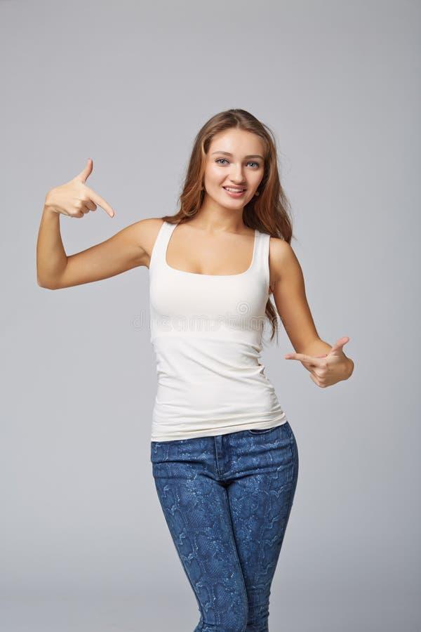 Glimlachende vrouw die op zich toejuichen richten gelukkig, op grijze backgr royalty-vrije stock afbeelding