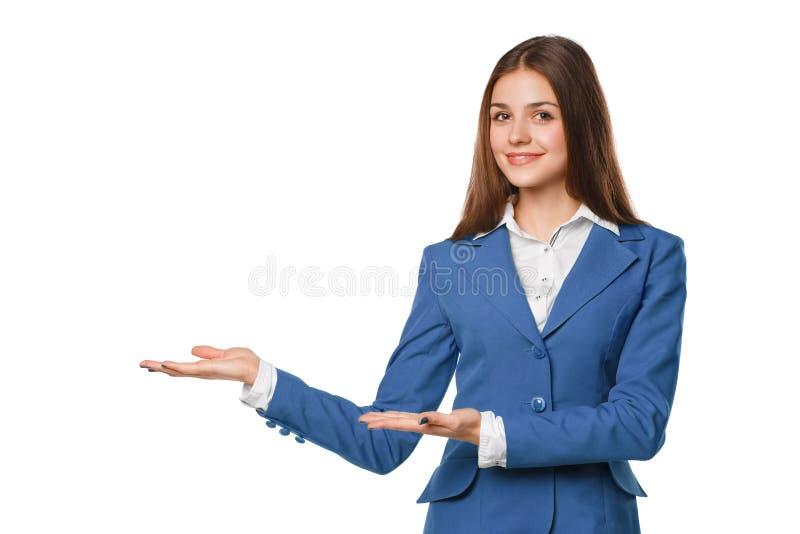 Glimlachende vrouw die open handpalm met exemplaarruimte tonen voor product of tekst Bedrijfsvrouw in blauw die kostuum, over wit royalty-vrije stock afbeelding