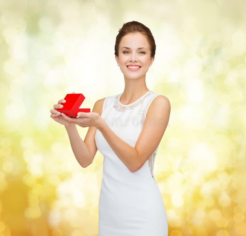 Glimlachende vrouw die rode giftdoos houden stock foto