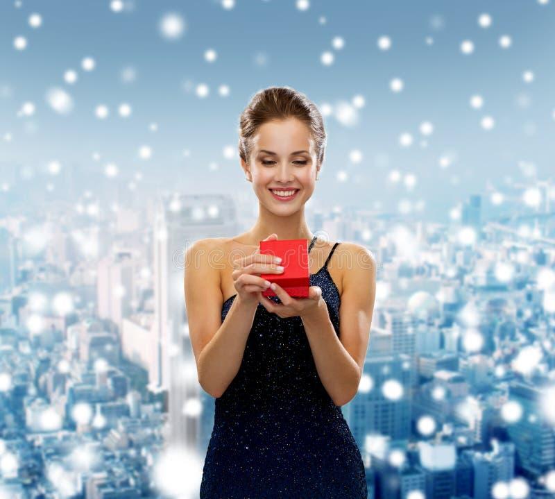 Glimlachende vrouw die rode giftdoos houden stock afbeelding