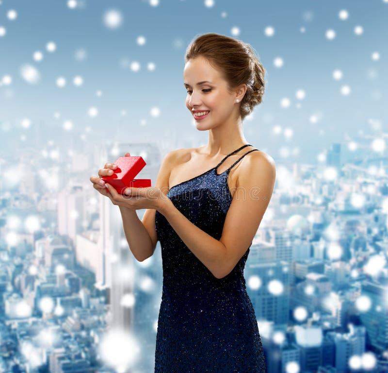Glimlachende vrouw die rode giftdoos houden royalty-vrije stock afbeelding