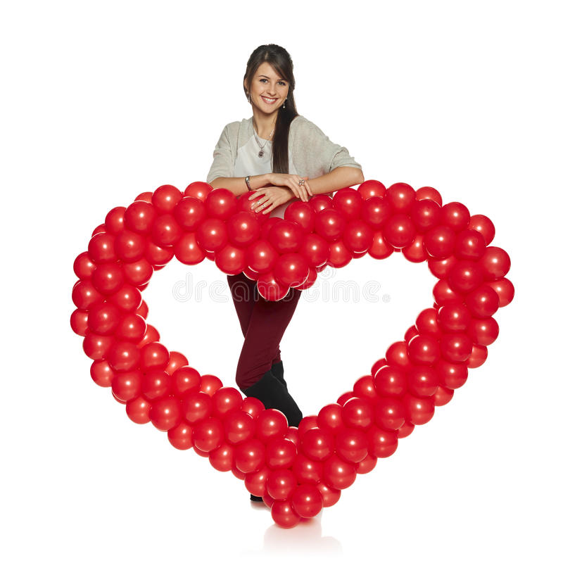 Glimlachende vrouw die rood ballonhart houden stock afbeeldingen