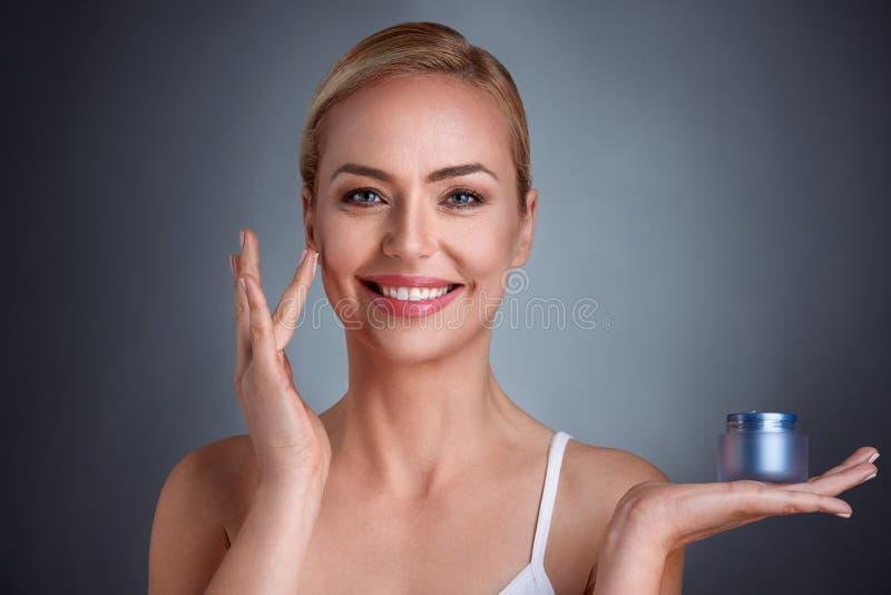 Glimlachende vrouw die room op gezicht toepassen stock fotografie