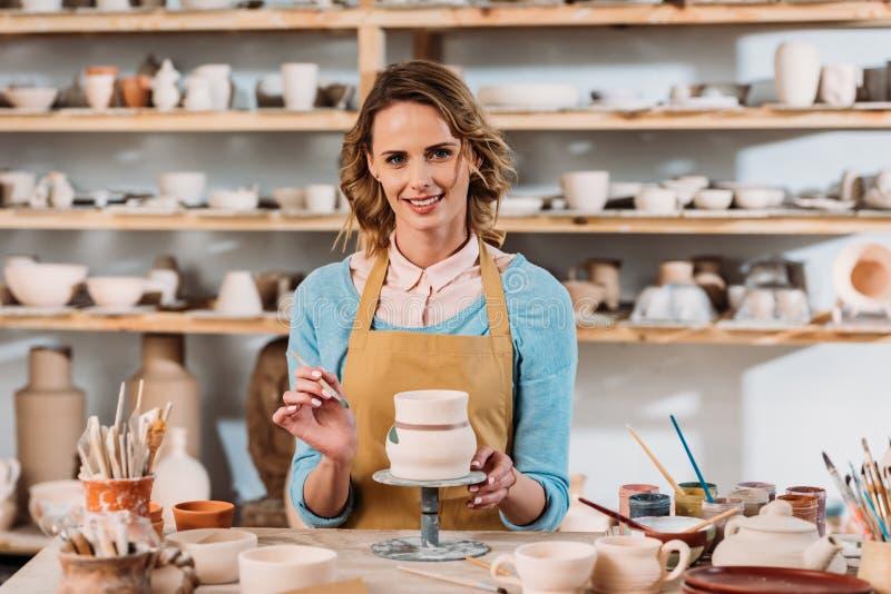glimlachende vrouw die in schort ceramische dishware schilderen royalty-vrije stock afbeelding