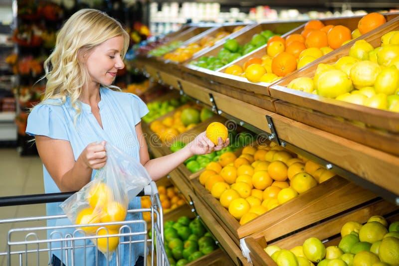 Glimlachende vrouw die sinaasappelen in plastic zak zetten stock fotografie