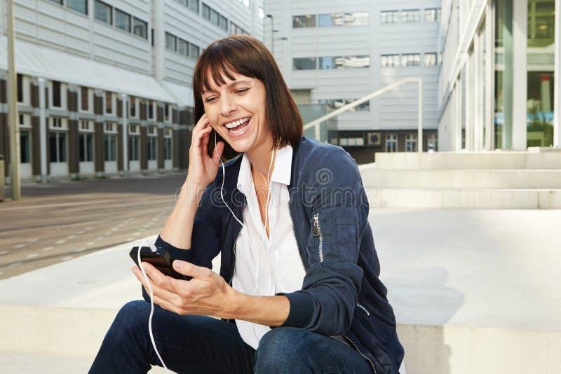Glimlachende vrouw die slimme telefoon met oortelefoons houden stock afbeelding