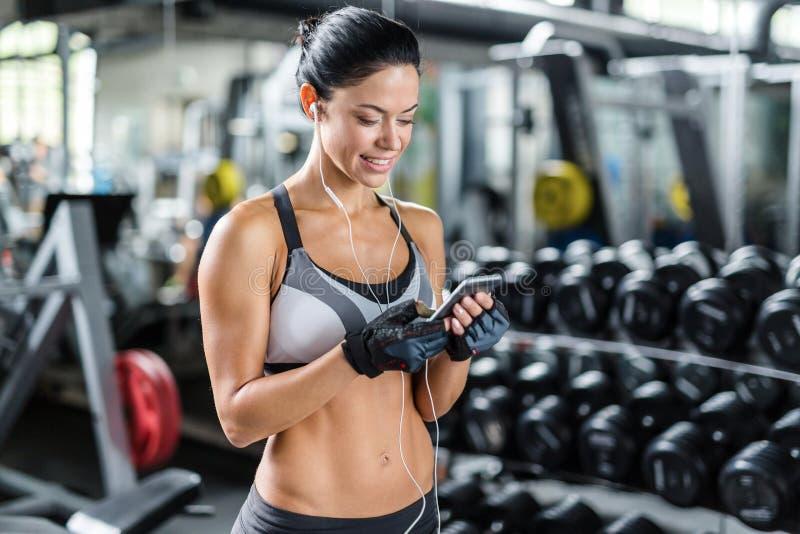 Glimlachende Vrouw die Smartphone in Gymnastiek gebruiken stock foto