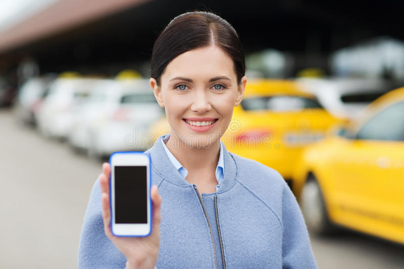 Glimlachende vrouw die smartphone over taxi in stad tonen stock fotografie