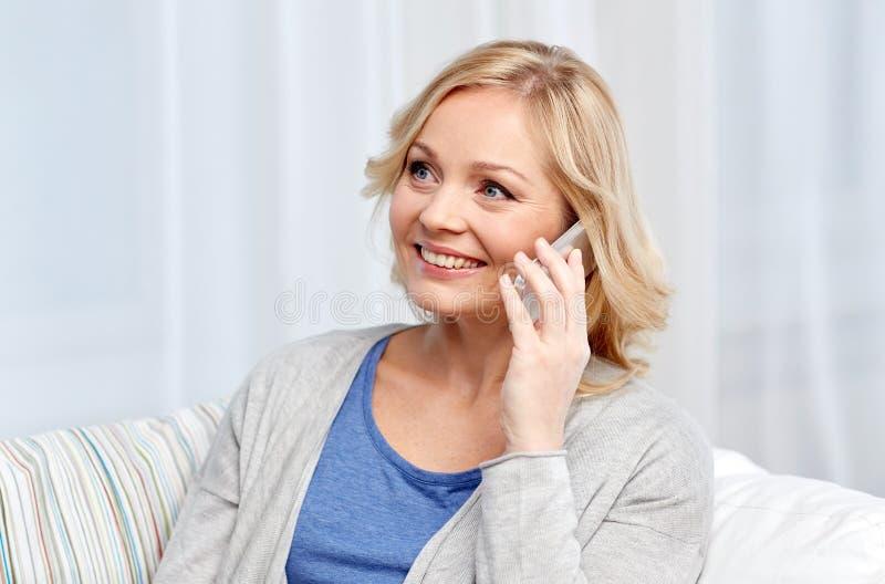 Glimlachende vrouw die smartphone thuis uitnodigen royalty-vrije stock afbeeldingen