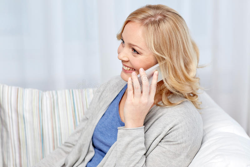 Glimlachende vrouw die smartphone thuis uitnodigen royalty-vrije stock foto's