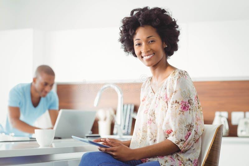 Glimlachende vrouw die tablet gebruiken stock afbeeldingen