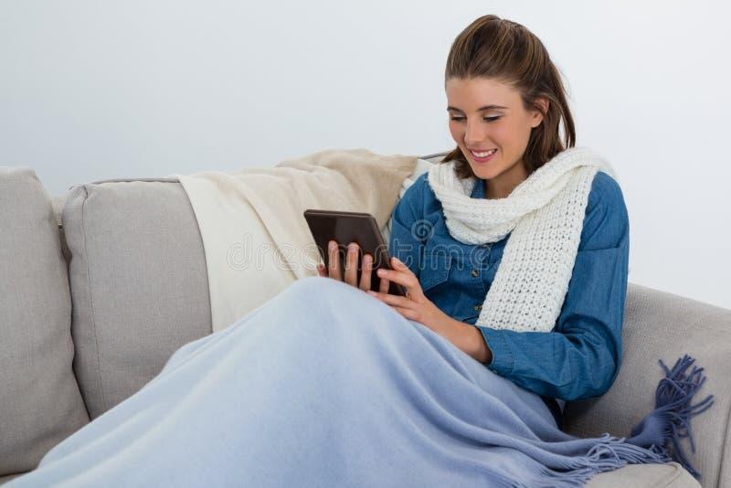 Glimlachende vrouw die tabletcomputer met behulp van terwijl het zitten op bank stock afbeeldingen