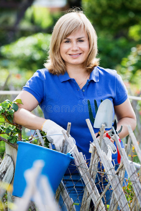 Glimlachende vrouw die tuinbouwhulpmiddelen in tuin op zonnig DA houden royalty-vrije stock foto's