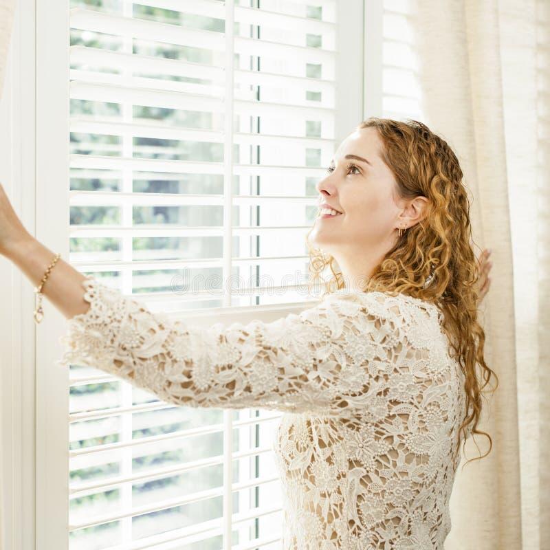 Glimlachende vrouw die uit venster kijken stock foto's