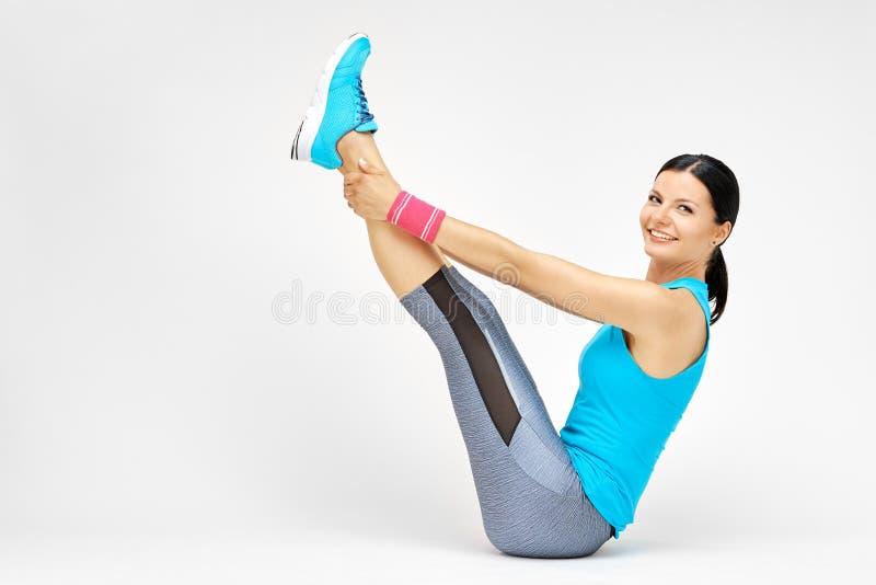 Glimlachende vrouw die uitrekkende pilates oefeningen doen bij de gymnastiek stock foto's