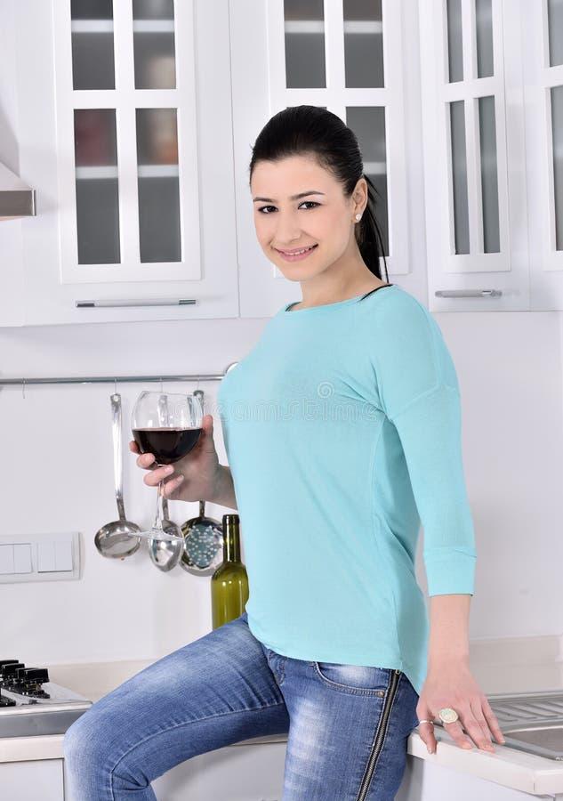 Glimlachende vrouw die van rode wijnstok in de keuken genieten stock foto