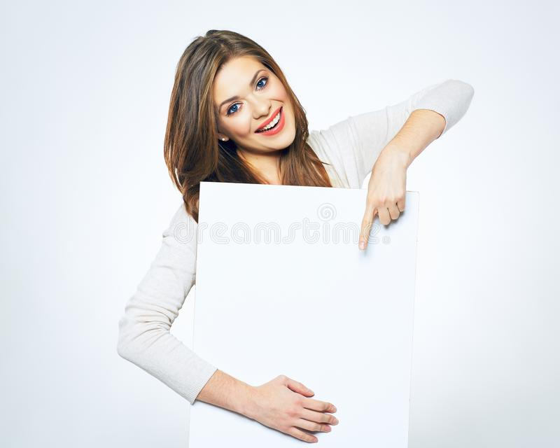 Glimlachende vrouw die vinger op wit leeg adreskaartje richten stock foto