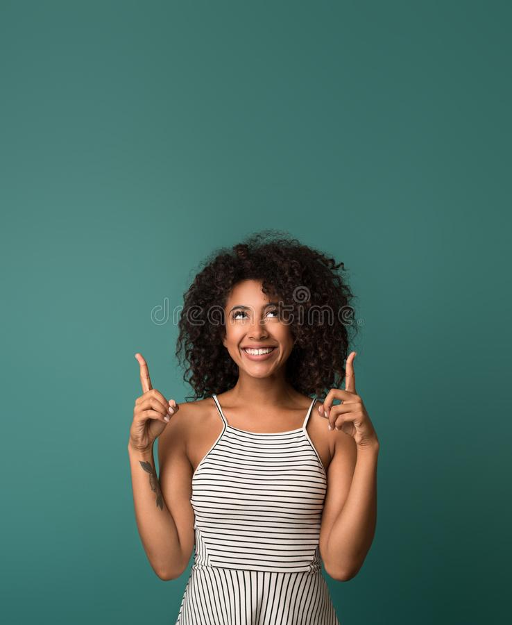 Glimlachende vrouw die vingers over blauwe achtergrond benadrukken stock fotografie