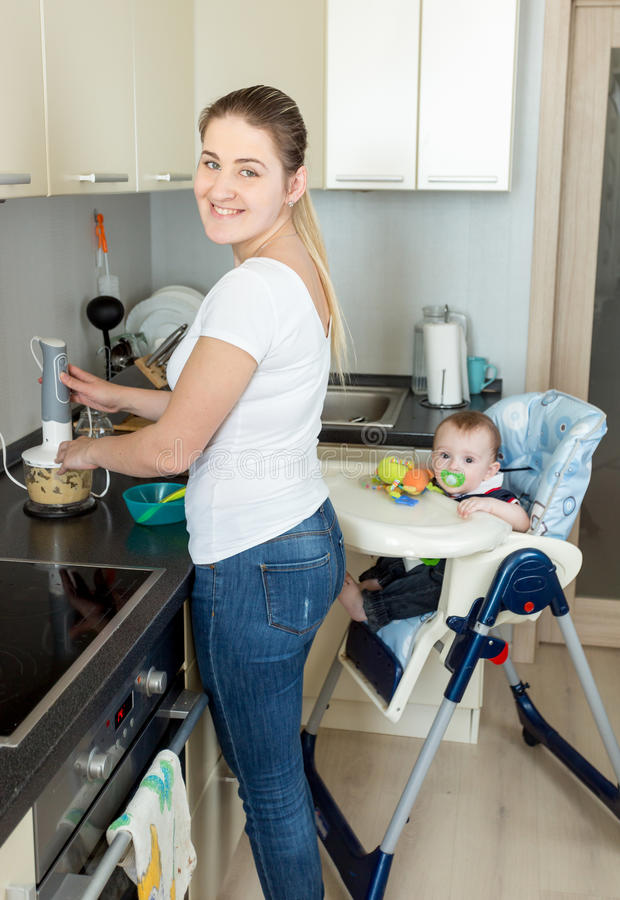 Glimlachende vrouw die voedsel voor haar jongen van de 9 maanden oudbaby voorbereiden royalty-vrije stock fotografie