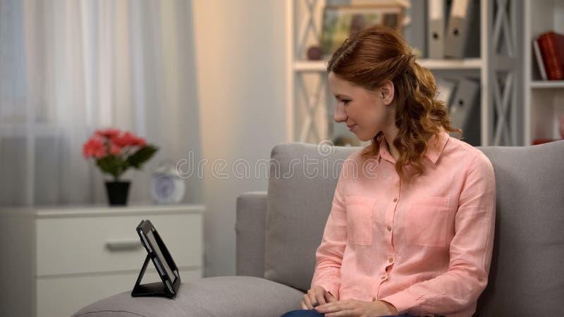 Glimlachende vrouw die vriend via lusjezitting roepen op bank die thuis, op film letten royalty-vrije stock foto