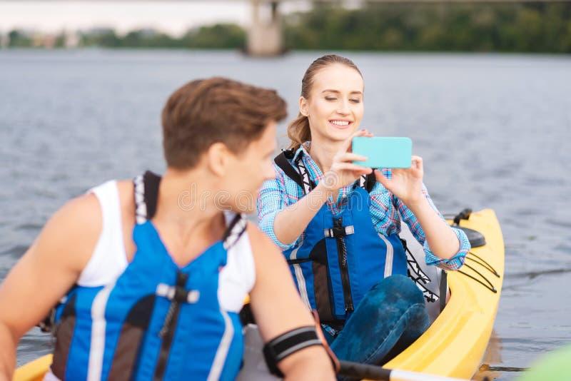 Glimlachende vrouw die vrolijk terwijl het maken van foto van rivier voelen royalty-vrije stock foto