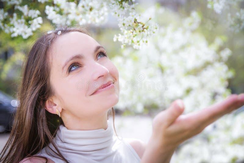 Glimlachende vrouw die witte bloemblaadjes vangen stock fotografie