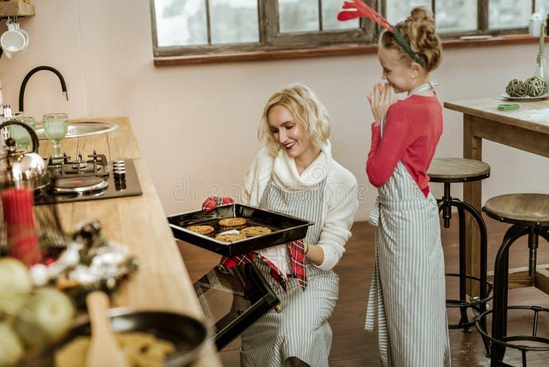 Glimlachende vrouw die in witte sweater haar dochter controleren royalty-vrije stock fotografie