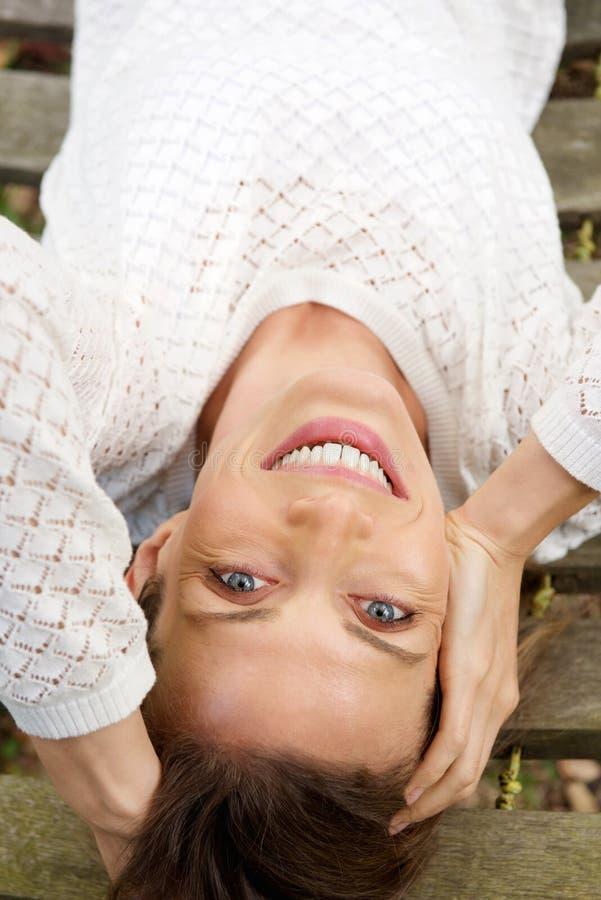 Glimlachende vrouw die in witte sweater op hangmat liggen royalty-vrije stock foto's