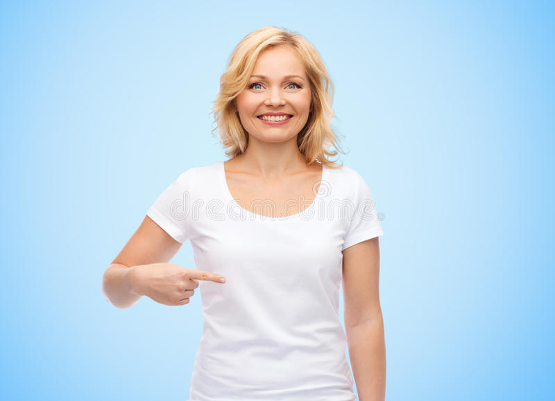 Glimlachende vrouw die in witte t-shirt aan zich richten stock foto