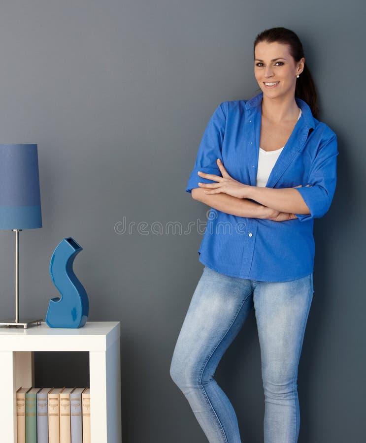 Glimlachende vrouw die zich bij woonkamermuur bevindt stock foto's