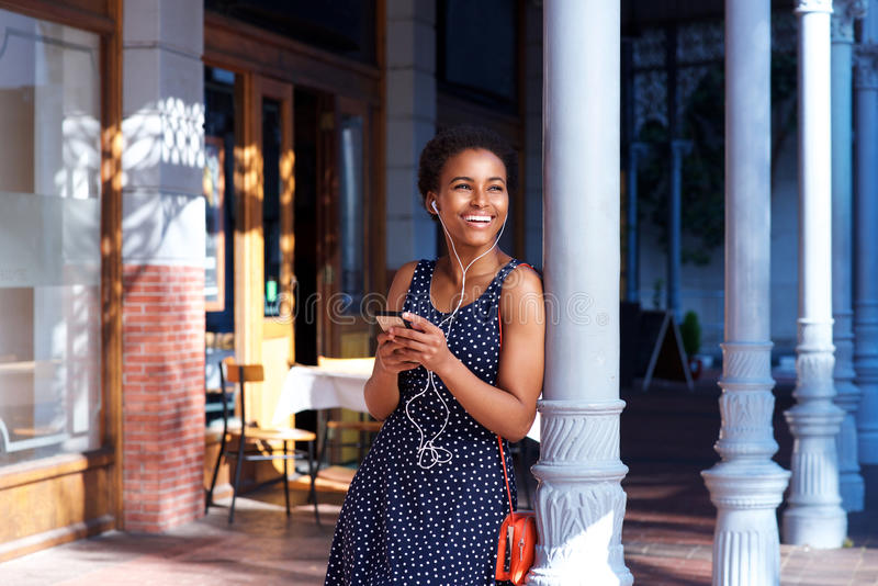 Glimlachende vrouw die zich buiten met oortelefoons en mobiele telefoon bevinden stock afbeeldingen