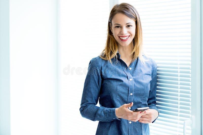 Glimlachende vrouw die zich door venster bevinden royalty-vrije stock foto