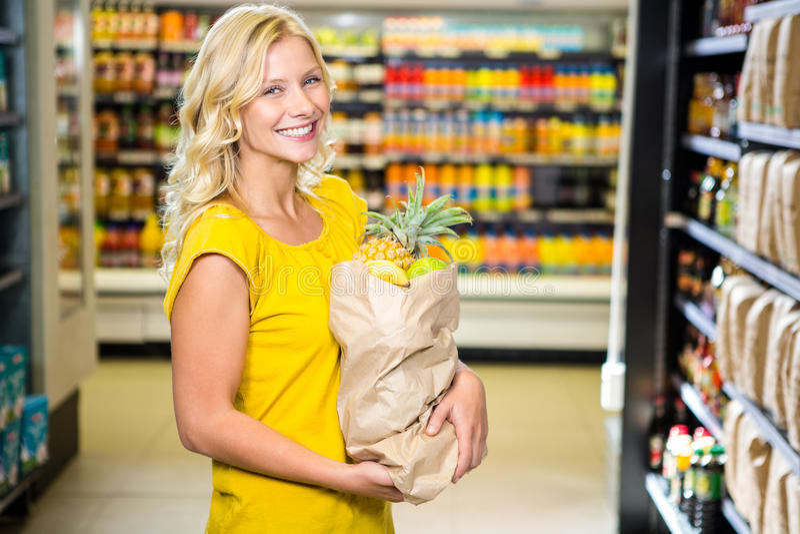 Glimlachende vrouw die zich in doorgang met kruidenierswinkelzak bevinden stock afbeeldingen