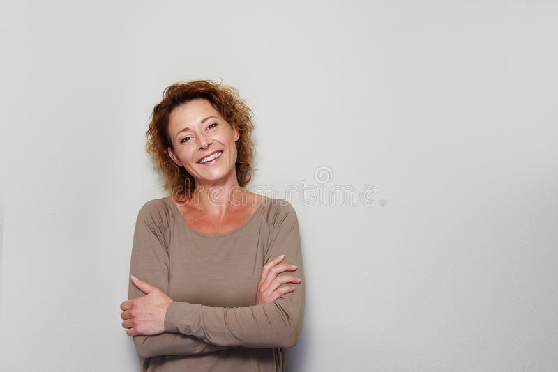Glimlachende vrouw die zich met gekruiste wapens bevinden stock afbeelding