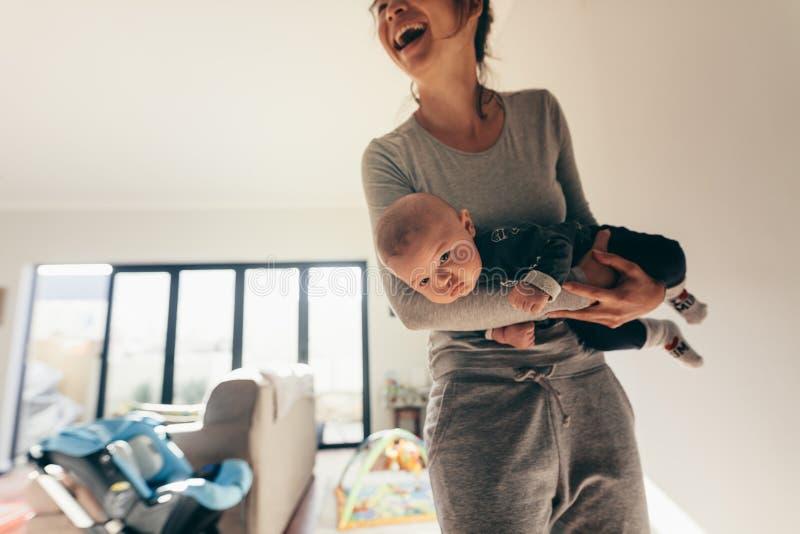 Glimlachende vrouw die zich in ruimte met haar baby bevinden stock afbeeldingen