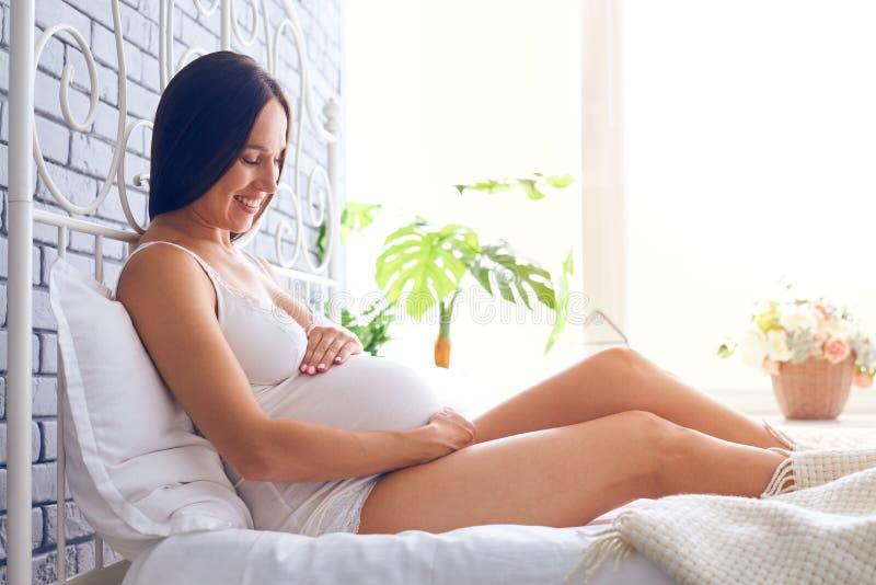 Glimlachende vrouw die zwangere buik na het wekken bekijkt stock foto's