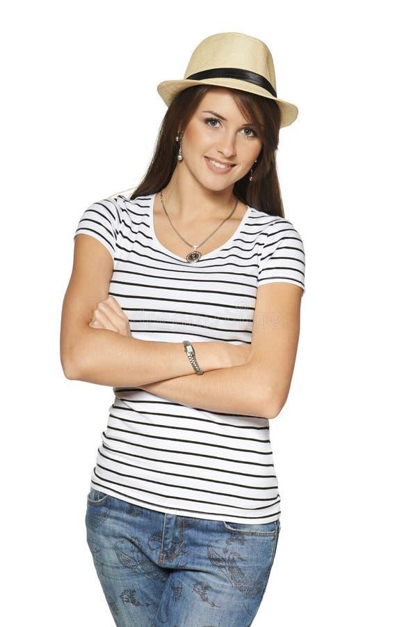Glimlachende vrouw in gestripte t-shirt en strohoed stock foto