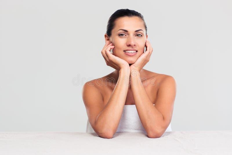 Glimlachende vrouw in handdoekzitting bij de lijst stock foto
