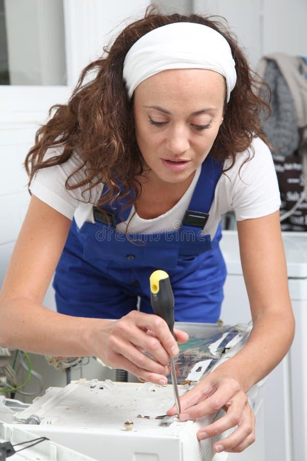 Glimlachende vrouw het bevestigen wasmachine royalty-vrije stock afbeeldingen