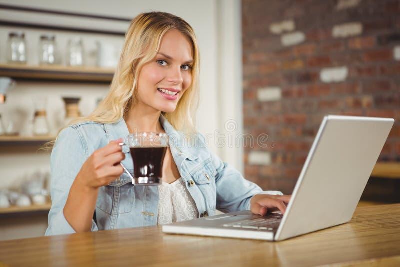 Glimlachende vrouw het drinken koffie en het typen op laptop stock afbeelding