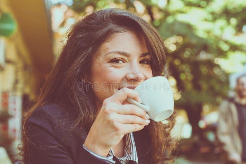 Glimlachende vrouw het drinken koffie Het genieten van in koffie royalty-vrije stock foto