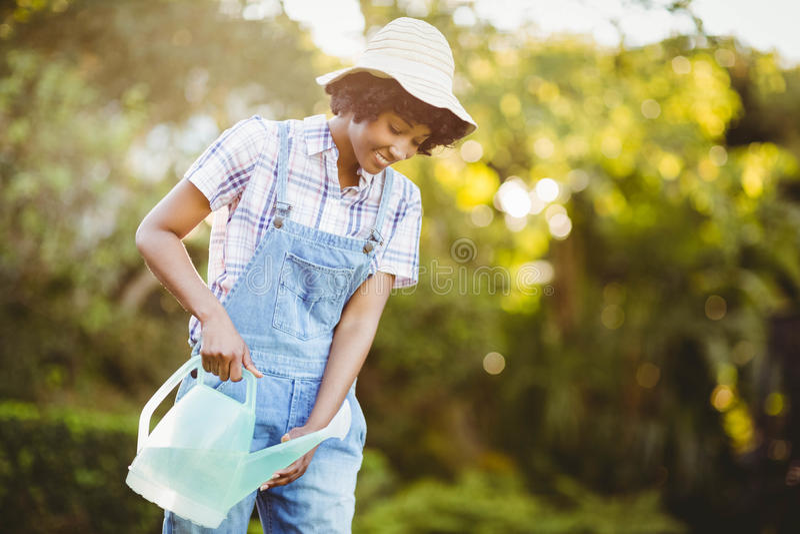 Glimlachende vrouw het water geven installaties royalty-vrije stock afbeeldingen