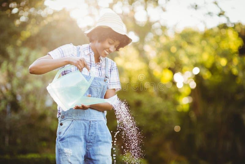 Glimlachende vrouw het water geven installaties stock foto's
