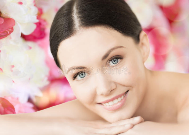 Glimlachende vrouw in kuuroord die op het massagebureau liggen stock afbeeldingen